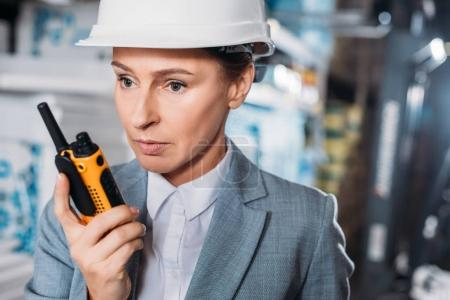 female inspector in helmet with walkie talkie in warehouse