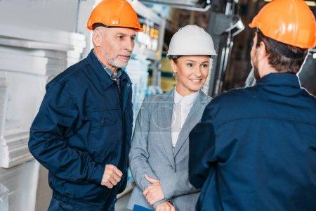 Foto de Los trabajadores masculinos y femenino inspector en cascos en almacén - Imagen libre de derechos