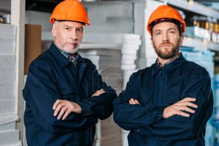 male workers in helmets posing with crossed arms in storehouse