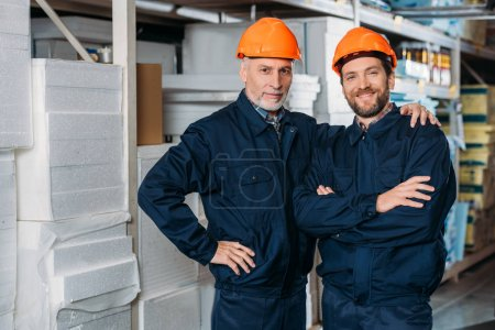 male workers in helmets hugging and posing in storehouse
