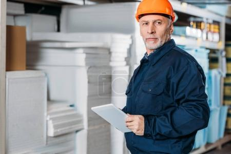 Photo for Senior male worker in helmet with digital tablet in shipping stock - Royalty Free Image