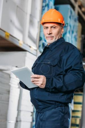 senior male worker in helmet with digital tablet in shipping stock