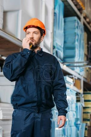 Photo pour Male worker in helmet with walkie talkie in shipping stock - image libre de droit
