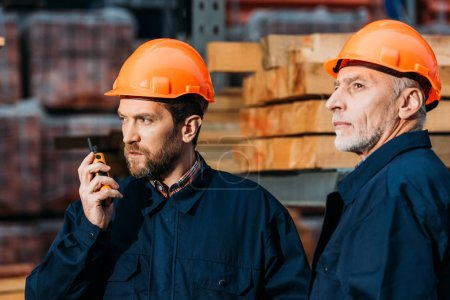 Photo for Builders in hardhats working with walkie talkie outside on construction - Royalty Free Image