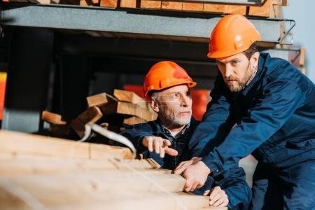 two builders in helmets working with wooden planks outside on construction