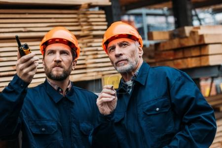 two builders in helmets working outside on construction