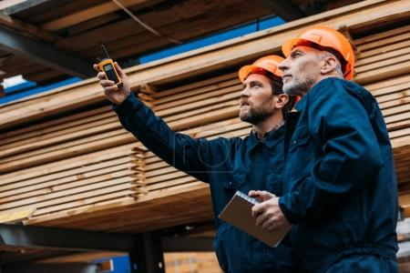 Photo for Builders in helmets pointing with walkie talkie on construction - Royalty Free Image