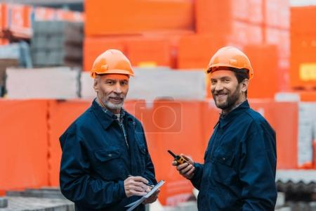Photo for Two builders in helmets working with walkie talkie and notepad outside on construction - Royalty Free Image