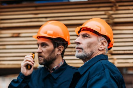 Photo for Two builders in helmets working with walkie talkie outside on construction - Royalty Free Image