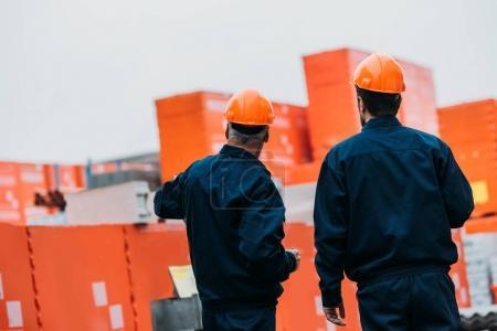Photo pour Vue arrière de deux constructeurs de casques travaillant à l'extérieur sur la construction - image libre de droit