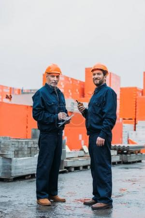 Photo for Builders in helmets working with walkie talkie and notepad outside on construction - Royalty Free Image