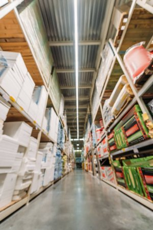 Photo pour Blurred view of shelves with boxes in storehouse - image libre de droit
