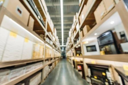 Photo for Blurred view of shelves with boxes in warehouse - Royalty Free Image