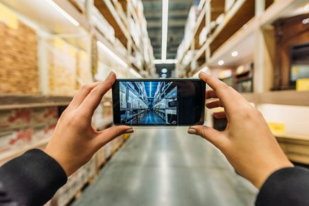 Photo for Cropped view of person taking photo of shipping stock on smartphone, Camera point of view - Royalty Free Image