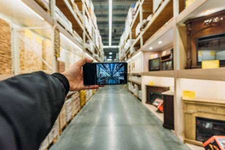 Photo for Cropped view of person taking photo of storage on smartphone, Camera point of view - Royalty Free Image