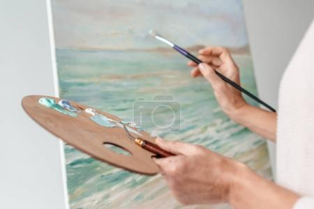 Photo for Cropped shot of artist holding palette and paintbrush while painting at easel in art studio - Royalty Free Image