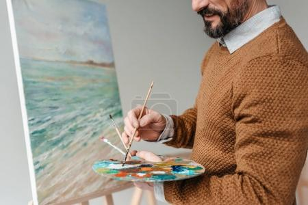 Photo for Cropped shot of bearded man holding palette and painting on easel at art class - Royalty Free Image