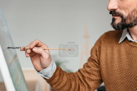 Photo for Cropped shot of bearded man painting on easel at art class - Royalty Free Image