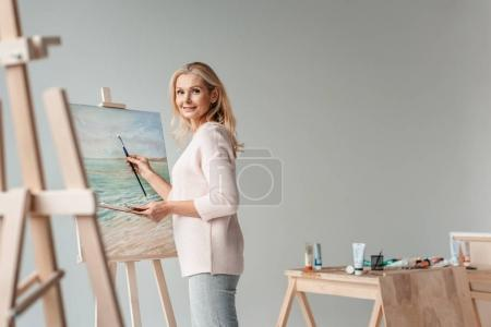 Photo for Mature female artist smiling at camera while painting on easel in art studio - Royalty Free Image