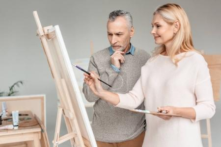 senior man looking at easel while smiling mature woman painting on it during art class