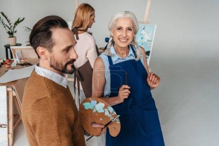 cheerful senior woman holding paintbrush and smiling at camera at art class