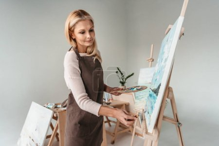 Photo for Beautiful mature woman in apron painting on easel at art class - Royalty Free Image