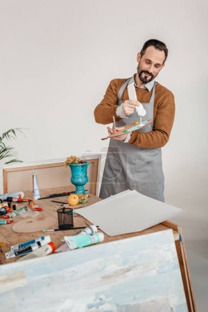 Photo for Smiling mature male artist in apron holding palette in art studio - Royalty Free Image