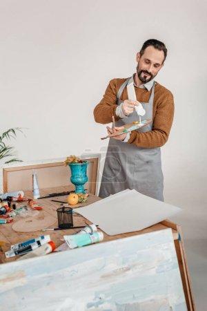 Photo pour Souriant mature artiste masculin en tablier tenant la palette dans l'atelier d'art - image libre de droit