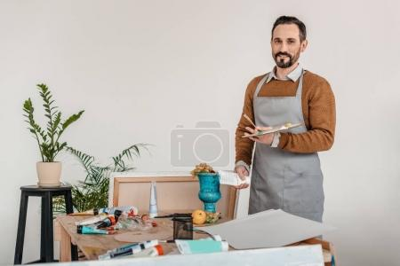 handsome mature male artist in apron holding palette and smiling at camera