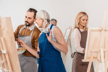 adult students in aprons painting on easels during art class