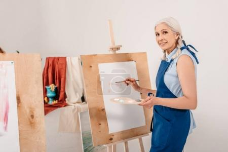 beautiful senior woman smiling at camera while painting on easel in art studio