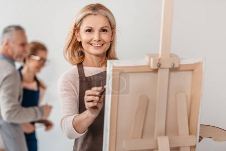 beautiful mature woman smiling at camera while painting on easel at art class
