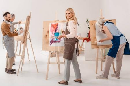 Photo for Male and female adult students in aprons painting together on easels in art class - Royalty Free Image
