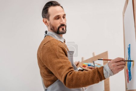Photo for Mature male artist holding palette and painting in art studio - Royalty Free Image