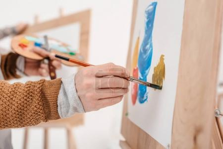 Photo for Cropped shot of person holding paintbrush and painting on easel - Royalty Free Image