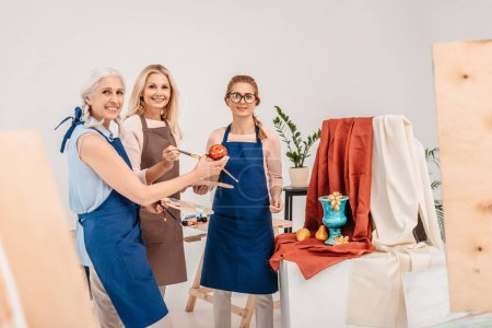 three female artists smiling at camera and ready to paint still life in art studio