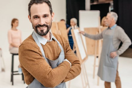 Photo for Handsome mature artist smiling at camera in art studio - Royalty Free Image