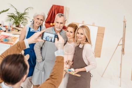 man with smartphone photographing senior and mature students at art class