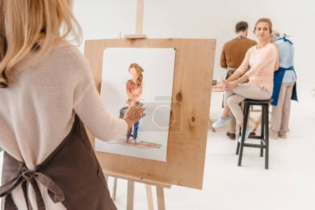 cropped shot of woman painting on easel while model sitting on chair in art studio