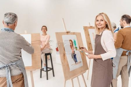 Photo for Mature woman smiling at camera while painting on easel at art class - Royalty Free Image