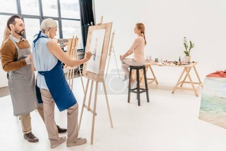 Photo for Senior artists painting portrait on easels at art class - Royalty Free Image