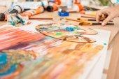 """Постер, картина, фотообои """"обрезать снимок руки человека и палитра с красками на столе"""""""