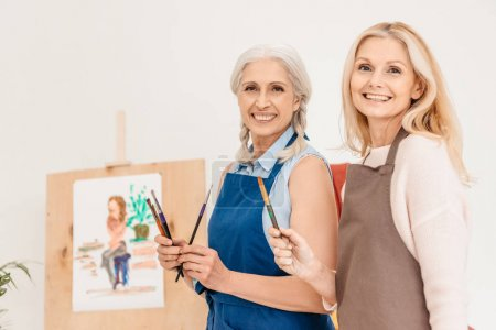 cheerful senior women smiling at camera and holding paint brushes at art class