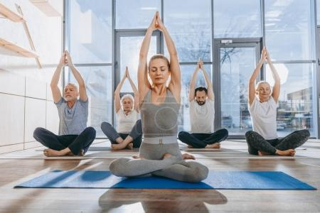 group of senior people practicing yoga with instructor in lotus pose on mats in studio