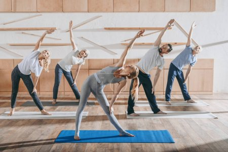 group of senior people stretching with instructor on mats in studio