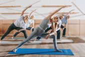 group of senior people practicing yoga and stretching with instructor on mats in studio