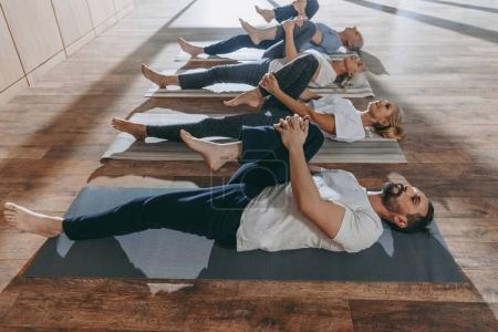 Photo pour Groupe de personnes âgées étirant dans des tapis de yoga en studio - image libre de droit