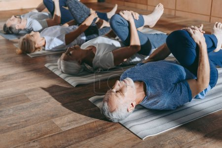 Photo for Group of senior people stretching in yoga mats in studio - Royalty Free Image