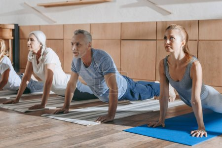 Photo for Group of senior people practicing yoga in dog pose on mats in studio - Royalty Free Image