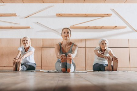 group of women practicing yoga and stretching on mats in studio